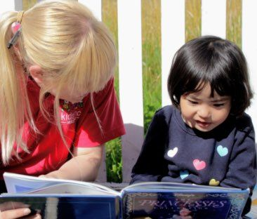 day nursery staff and child reading